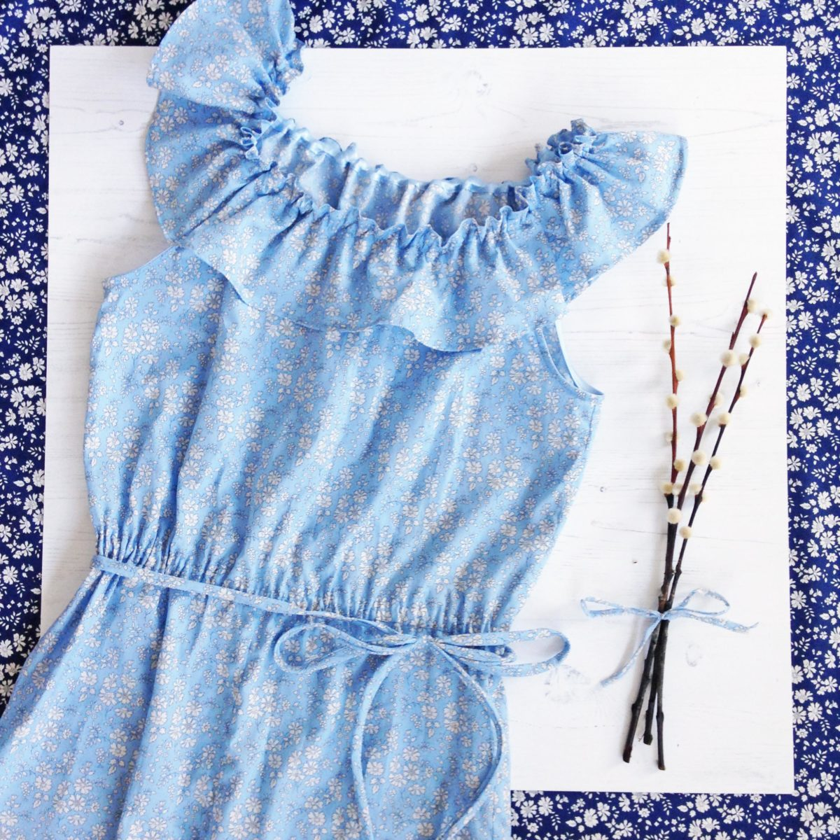 Blue cotton romper with ruffled collar in liberty